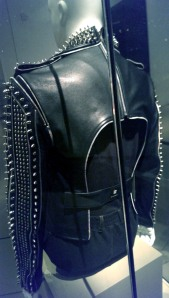 Mannequin wearing a hip leather jacket -- the back view shows that the sleeves are attached by zippers (to make it easier to remove and put on) , the back is cut out for comfort and a seat belt can slip over the wearer's waist under the jacket.