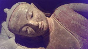 A frontal view of the Buddha's face as the figure lies on his side, eyes almost closed, relaxed yet attentive