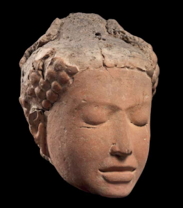 Head of a Buddha in terra-cotta, eyes closed, with its eye brows ever so slightly in tension