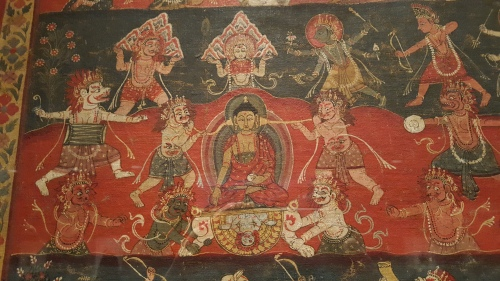 the detail shows the Buddha sitting in full lotus, one hand reaching down to the earth while two demons, one on either side of him, blow trumpets right into his ears.