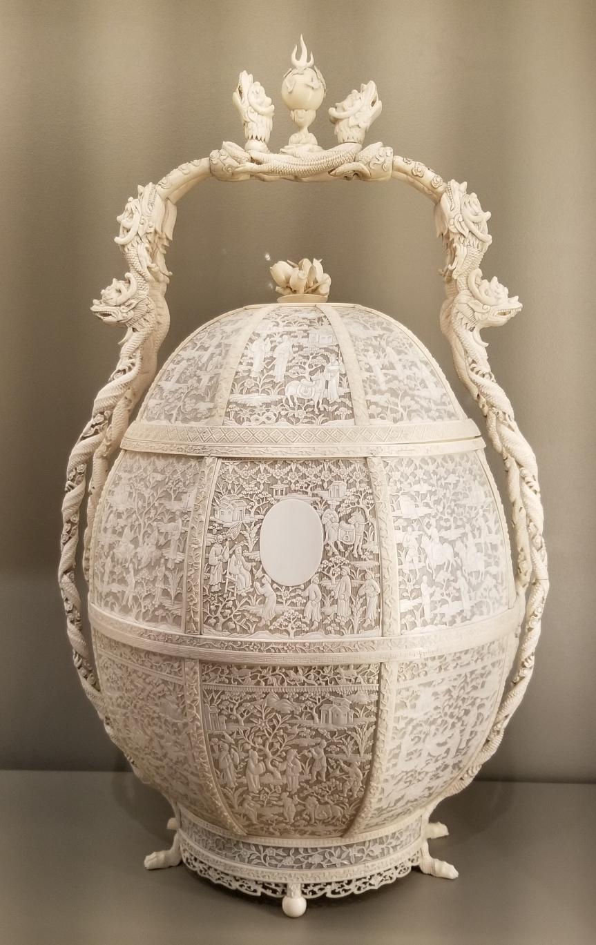 Egg-shaped basket entirely carved out of ivory, the body a delicate mesh with with scenes.